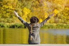 帽子的女孩坐船坞 举起手来 秋天日 backarrow 库存图片