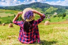 帽子的女孩坐草 免版税库存照片