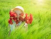 帽子的女孩用鸦片花束在绿色黑麦的领域的盖她的面孔 免版税库存照片