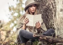 帽子的女孩读一本书的在秋天森林里 库存照片
