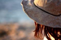 帽子的女孩 背景蓝色被弄脏的和布朗 库存照片