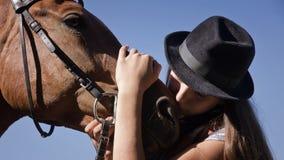 帽子的女牛仔与海湾马 免版税库存图片