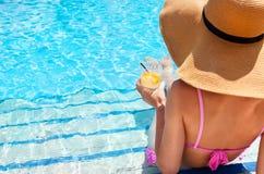 帽子的妇女享用在游泳池的鸡尾酒 免版税库存照片