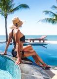 帽子的妇女在扣杆和游泳池附近晒日光浴 库存图片
