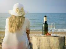 帽子的妇女在有一个开放瓶的海香槟和两块玻璃 图库摄影