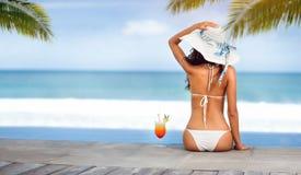 帽子的妇女在海滩的海附近与热带鸡尾酒 库存照片