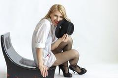 帽子的妇女在白色背景隔绝的椅子 图库摄影