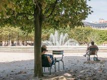 帽子的妇女在皇家宫殿,巴黎中读在树下 免版税库存照片