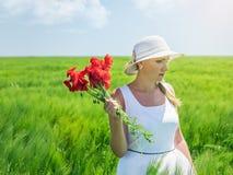 帽子的妇女在黑麦的一个绿色领域去 免版税库存照片