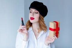 帽子的妇女有唇膏和圣诞节礼物盒的 库存照片