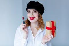 帽子的妇女有唇膏和圣诞节礼物盒的 免版税库存图片