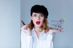 帽子的妇女有构成和购物车的唇膏的 免版税库存图片
