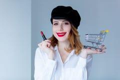 帽子的妇女有构成和购物车的唇膏的 免版税库存照片
