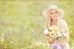 帽子的妇女有花花束的,时装模特儿夏天领域 免版税图库摄影