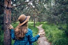 帽子的妇女用核桃在森林里 免版税库存图片