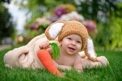 帽子的婴孩喜欢与红萝卜玩具的一个兔宝宝在绿草室外 库存照片