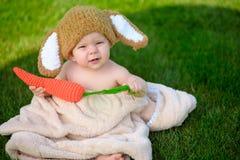 帽子的婴孩喜欢与红萝卜玩具的一个兔宝宝在绿草室外 图库摄影