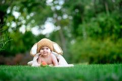 帽子的婴孩喜欢与红萝卜玩具的一个兔宝宝在绿草户外 图库摄影