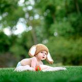 帽子的婴孩喜欢与红萝卜玩具的一个兔宝宝在绿草 库存图片