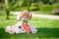 帽子的婴孩喜欢与红萝卜玩具的一个兔宝宝在绿草 免版税库存照片