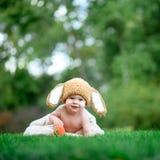 帽子的婴孩喜欢与红萝卜玩具的一个兔宝宝在绿草 图库摄影