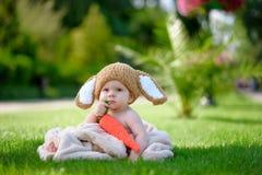 帽子的婴孩喜欢与红萝卜玩具的一个兔宝宝在绿草 库存照片