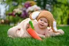 帽子的婴孩喜欢与红萝卜玩具的一个兔宝宝在绿草 免版税图库摄影
