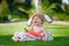 帽子的婴孩喜欢与红萝卜玩具的一个兔宝宝在绿草 免版税库存图片