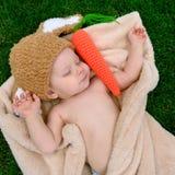 帽子的婴孩喜欢与红萝卜玩具的一个兔宝宝睡觉在绿草的 免版税库存图片