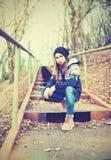 帽子的孤独的女孩少年坐台阶和哀伤的秋天 免版税库存图片