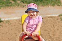 帽子的小女孩在儿童操场的跷跷板使用 图库摄影