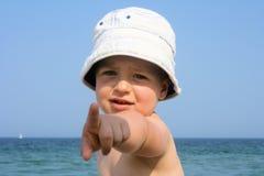 帽子的小男孩在海滩指向照相机的 库存图片