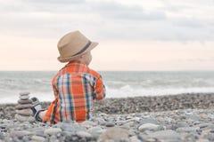 帽子的小男孩坐Pebble海滩 库存图片