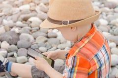 帽子的小男孩有在Pebble海滩的巧妙的电话的 免版税库存图片