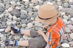 帽子的小男孩有在Pebble海滩的巧妙的电话的 图库摄影