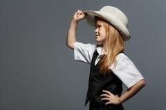 帽子的小逗人喜爱的女孩,在白色衬衣,在黑背心,看对边 隔绝在灰色 库存图片