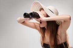 帽子的少妇有双筒望远镜的 库存照片