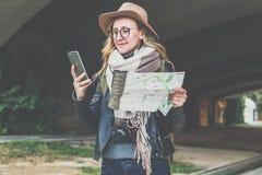 帽子的年轻微笑的妇女游人在街道上在她的手上时站立并且使用智能手机,当拿着目的地地图 库存图片
