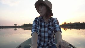 帽子的年轻愉快的女孩在有木桨的一条可膨胀的小船航行在湖 影视素材