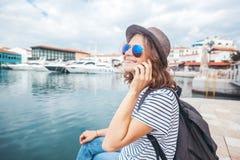 帽子的年轻美丽的妇女旅客谈话在一个流动响度单位 免版税库存图片