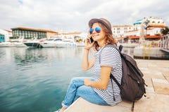 帽子的年轻美丽的妇女旅客谈话在一个流动响度单位 免版税库存照片