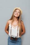 帽子的微笑的可爱的白肤金发的女孩有照片cmera身分的 免版税图库摄影