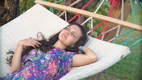 帽子的微笑的深色的妇女放松了和作梦在热带海滩的吊床 股票视频