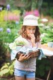 帽子的愉快的儿童女孩享受温暖的夏日的在开花的庭院里 图库摄影