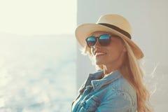 帽子的愉快的年轻旅客妇女在游轮 免版税库存图片