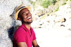 帽子的愉快的年轻人微笑对海滩的 库存图片