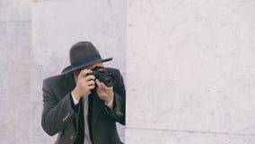 帽子的拍摄在照相机的年轻无固定职业的摄影师人特写镜头名人,当在墙壁后时的间谍 图库摄影