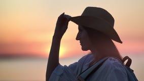 帽子的放松微笑的旅行的妇女敬佩在海的惊人的猩红色日落作梦和 影视素材