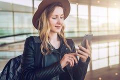 帽子的旅游妇女,有背包的在机场站立,使用智能手机 女孩检查电子邮件,聊天,浏览互联网 免版税库存照片