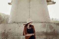 帽子的时髦的行家妇女有摆在河s附近的有风头发的 库存图片